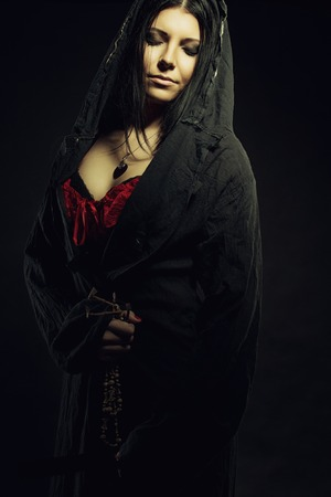 cowl: Pretty young girl in hood over dark background Stock Photo
