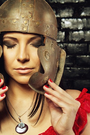 ancient sexy: Pretty sexy girl with ancient roman helmet posing over brick wall