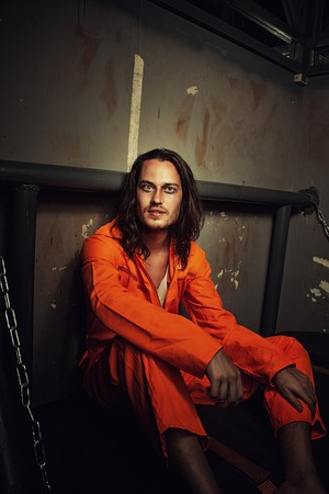 incarceration: Miserable prisoner in orange clothes sitting on a bed in his cell