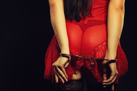 Seductive woman in red sexy dress posing over dark background in handcuffs Stock Photo