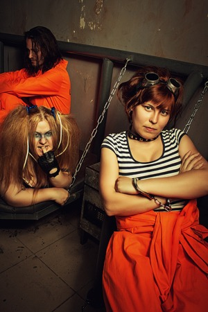 wicked problem: Three prisoners  in orange clothes sitting in a cell Stock Photo