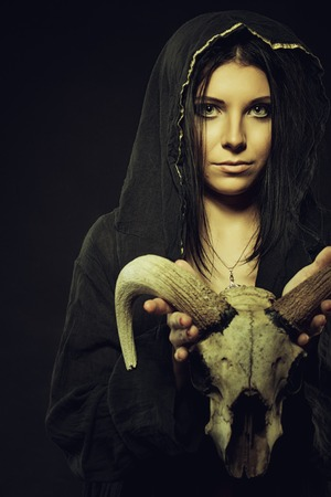 Pretty young girl in hood holding skull over dark background 版權商用圖片
