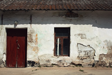 unevenness: Old grunged wall with window and red door.