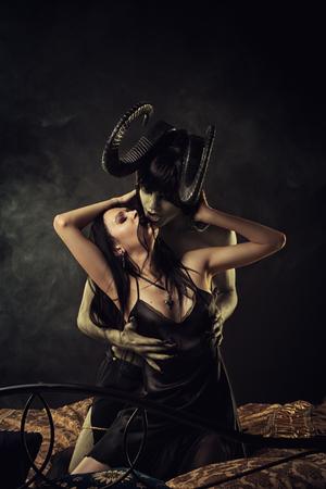Chica gótica atractiva en abrazo de demonio con cuernos horribles