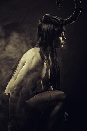infernal: Horrible horned demon posing in smoke over dark background Stock Photo