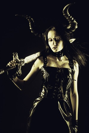 infernal: Pretty seductive horned girl with sword posing over dark background Stock Photo
