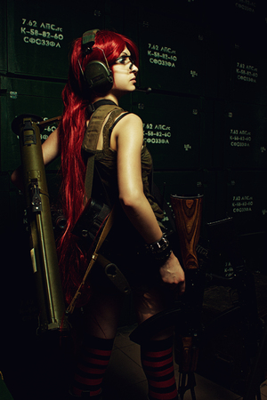 bazooka: Pretty redhead girl posing with bazooka and rifle in a dark storage