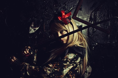 wicked woman: Cute girl with katana posing over dark background
