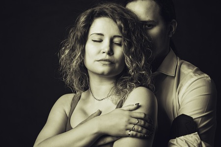seductive couple: Young guy hugging his girlfriend over dark background Stock Photo