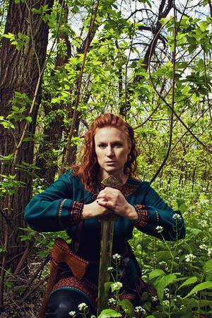 scandinavian girl: Redhead beautiful scandinavian girl posing in a forest with sword
