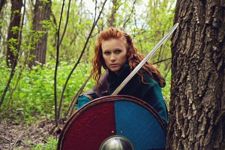 Redhead scandinavian young woman with sword and shield posing in a wood Stock Photo