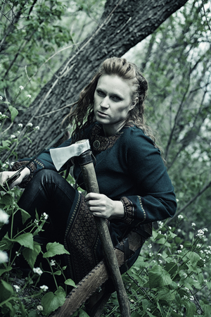 merciless: Serious redhead scandinavian woman posing with axe in a forest