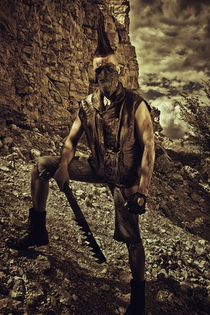 horrible: Cruel horrible post-apocalyptic raider with hand-made sword posing on a wasteland Stock Photo