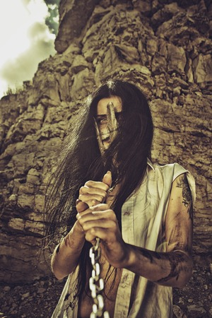 slave girl: Slave girl in iron mask holding her chains over wasteland of post-apocalyptic world Stock Photo