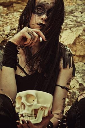 raider: Pretty sad raider posing with cigarette and skull Stock Photo
