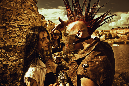 wasteland: Raider with mohawk hairstyle, young pretty slave  in iron mask and slave trader posing over post-apocalyptic wasteland.