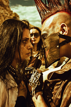 Mad merciless raider and young cute slave looking into each others eyes over post-apocalyptic wasteland.