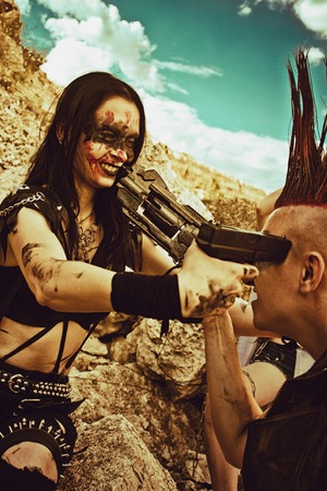 wasteland: Female merciless raider and male raider with mohawk haircut aiming each other with guns over post-apocalyptic wasteland.