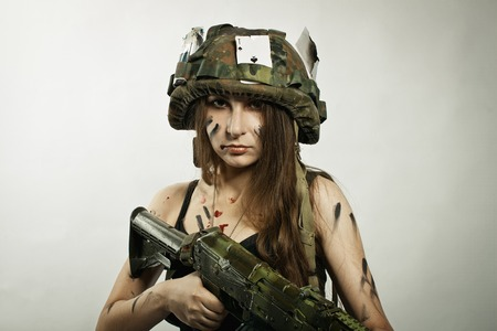 riffle: Pretty young girl in helmet with riffle over white background