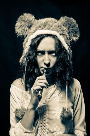 Angry girl in bear hat with vaporizer posing over dark background Stock Photo