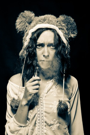 Sad girl in bear hat with vaporizer posing over dark background Stock Photo