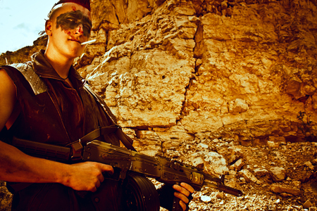 Merciless raider of post-apocalyptic wastelands posing with automatic rifle over rocks