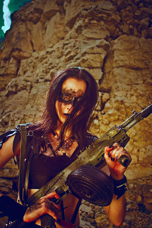 merciless: Pretty post-apocalyptic warrior posing over rocks with automatic rifle