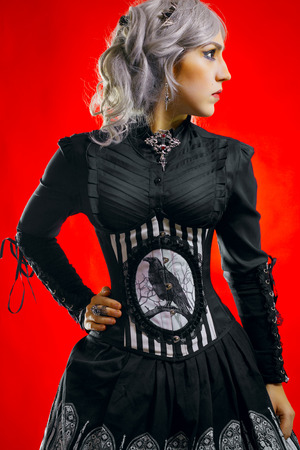 humility: Pretty gothic girl with black eyes standing over red background