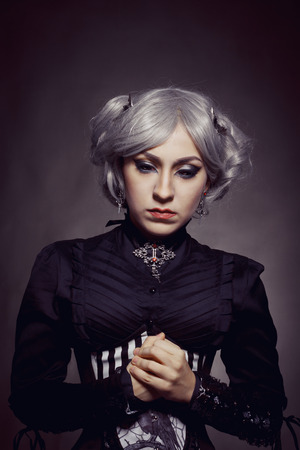 humility: Pretty old-fashioned gothic girl posing over dark background