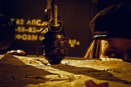guerilla: Female Che Guevara looking at grenade in a dark warehouse