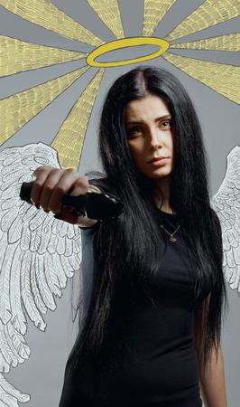 Pretty criminal girl posing with gun over grey background Stock Photo