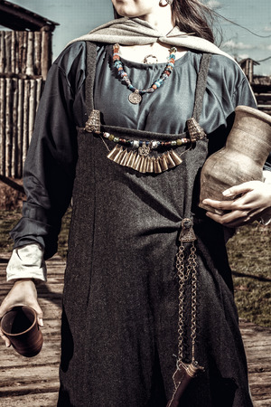 reenacting: Scandinavian middle class woman in  historical suit posing over village. Her apparel based on archaeological sites on  Island of Gotland. Late 10th - 11th centuries. Stock Photo