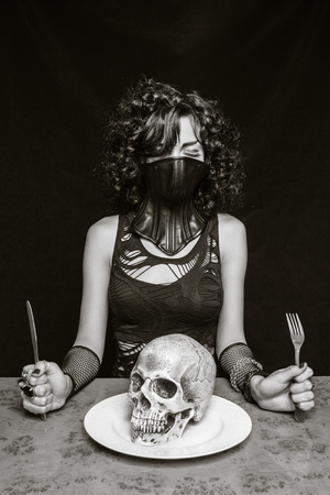 Gothic girl in bdsm mask with skull in her plate over dark background Stock Photo