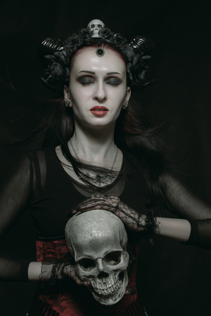 Young horned beautiful lady posing over dark background with skull Stock Photo