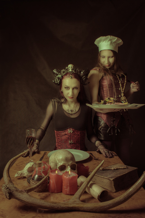Cook with main dish and her horned lord over dark background Stock Photo