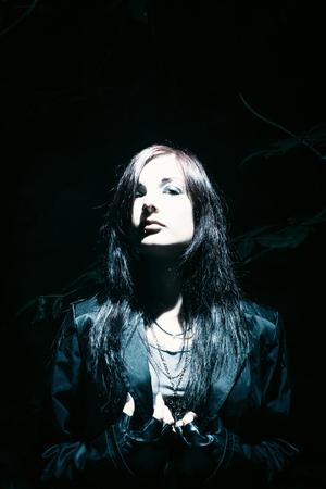 Brunette pretty gothic girl posing in a forest Stok Fotoğraf