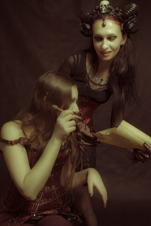 Gothic girl giving her signature to horned lady with contract