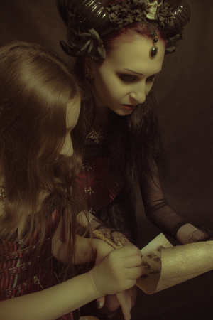 Gothic girl giving her signature to horned lady