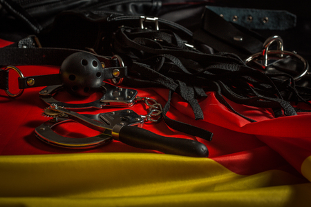 Bdsm toys for pain and pleasure laying on german flag Stock Photo