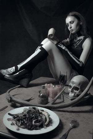 Beautiful gothic girl on a table writing a letter