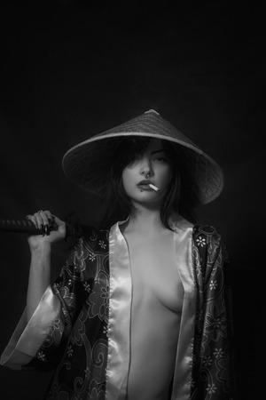 Naked samurai girl in farmer hat with katana