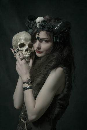 Cute horned asian girl holding skull over dark background