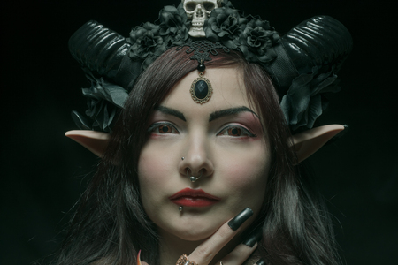 Horned asian girl with elvish ears over dark background