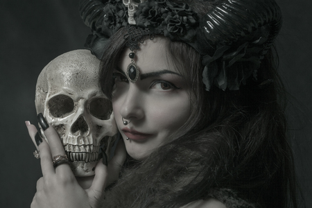 Horned asian cute girl with skull posing over dark background Stock Photo