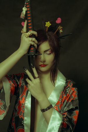 Seductive girl in kimono posing with katana over dark background