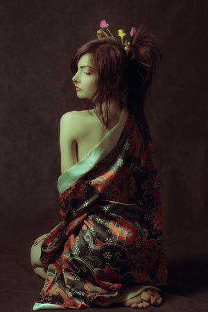 Pretty girl in kimono sitting on the floor. Rear view. Stok Fotoğraf - 100416338