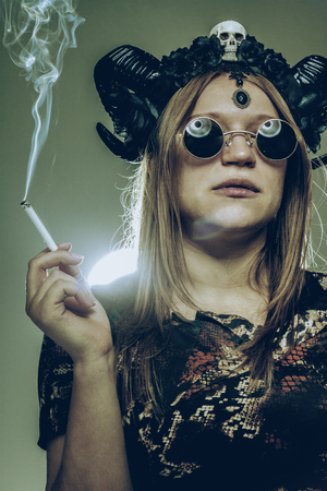 Serious brutal horned girl with cigarette over green