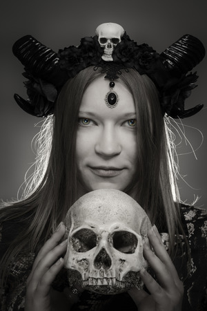 Portrait of pretty serious horned girl posing with skull