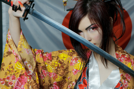 Cute girl in kimono posing over japanese flag with katana Banco de Imagens