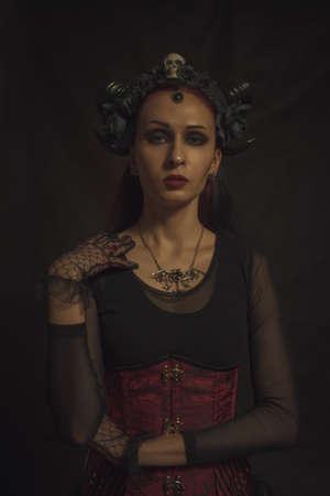 Horned gothic lady posing over dark background